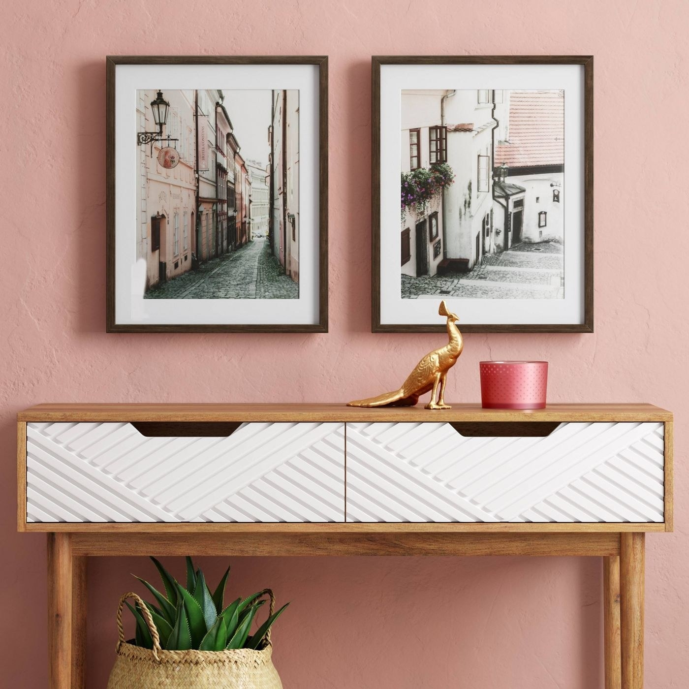 two framed photographs of city streets placed above a console table