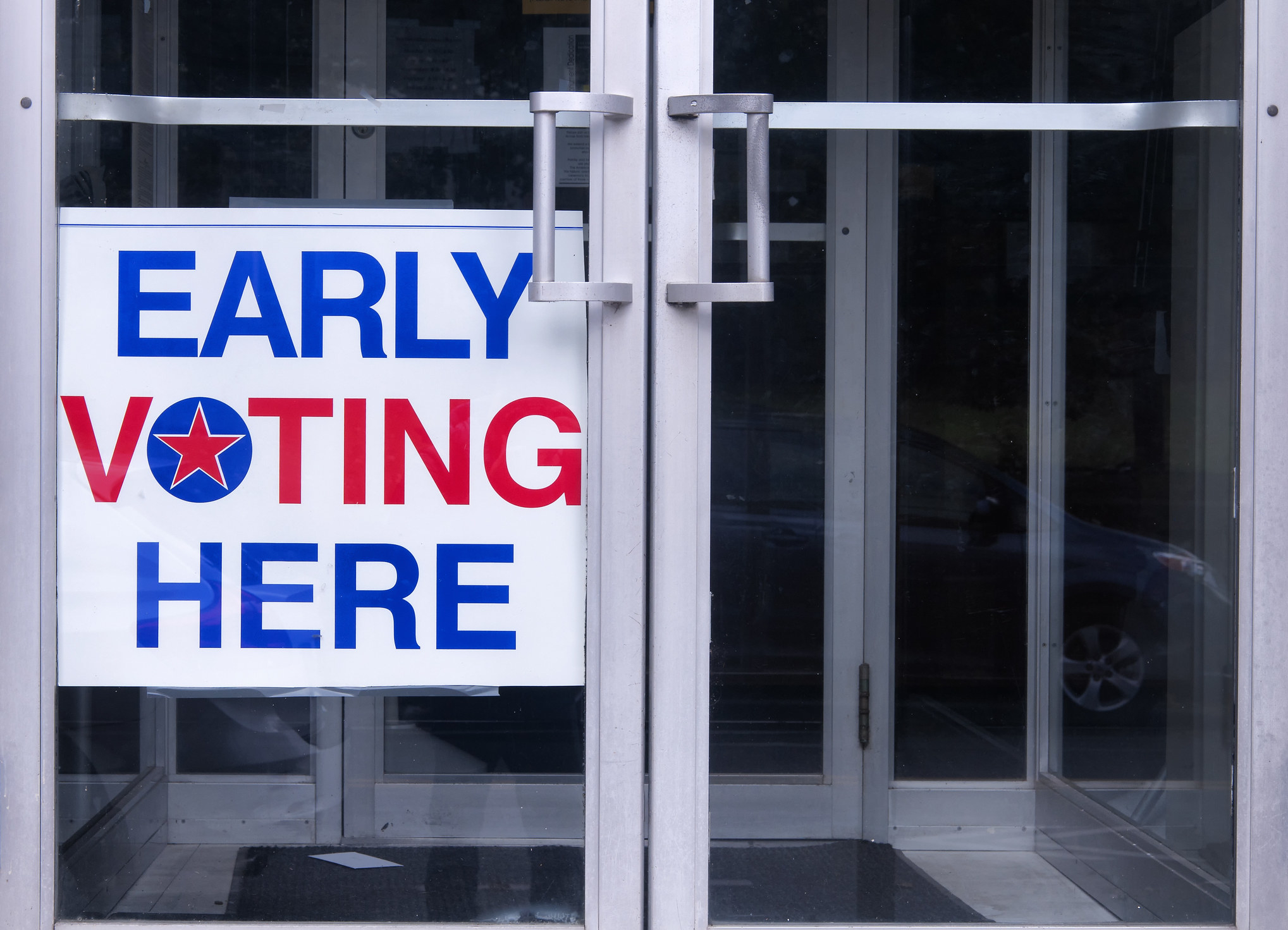 """A sign on the door of a building that reads """"EARLY VOTING HERE"""""""