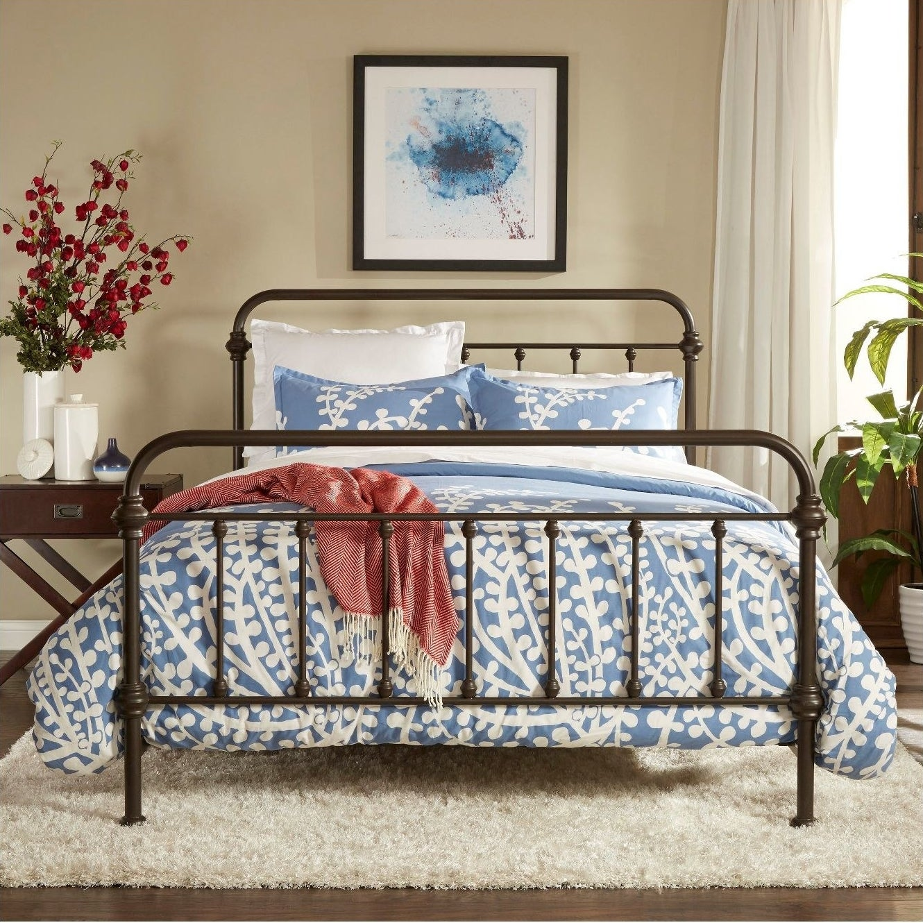 metal bed with blue comforter on it in the middle of a bedroom