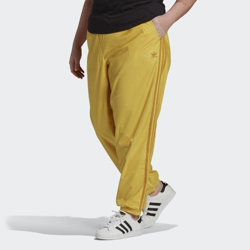 Model wears yellow adidas cuffed track pants with white and black sneakers