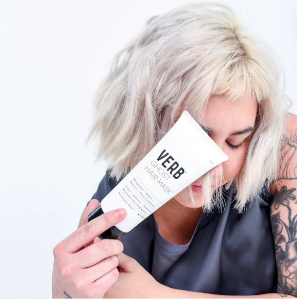 A person holds the hair mask against their short blonde bob