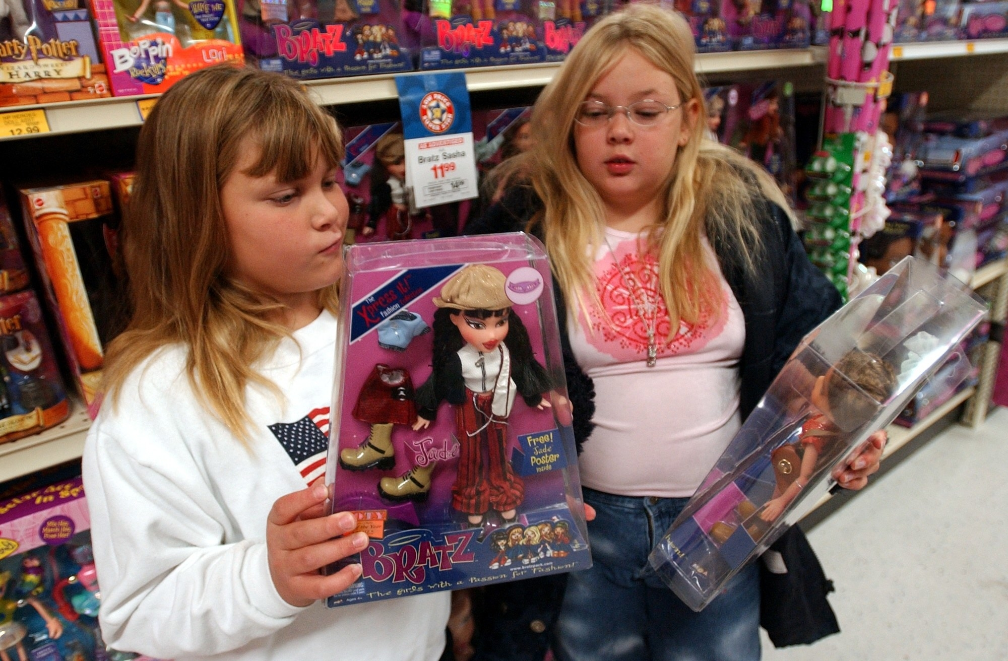 Two girls reading the back of Bratz doll box