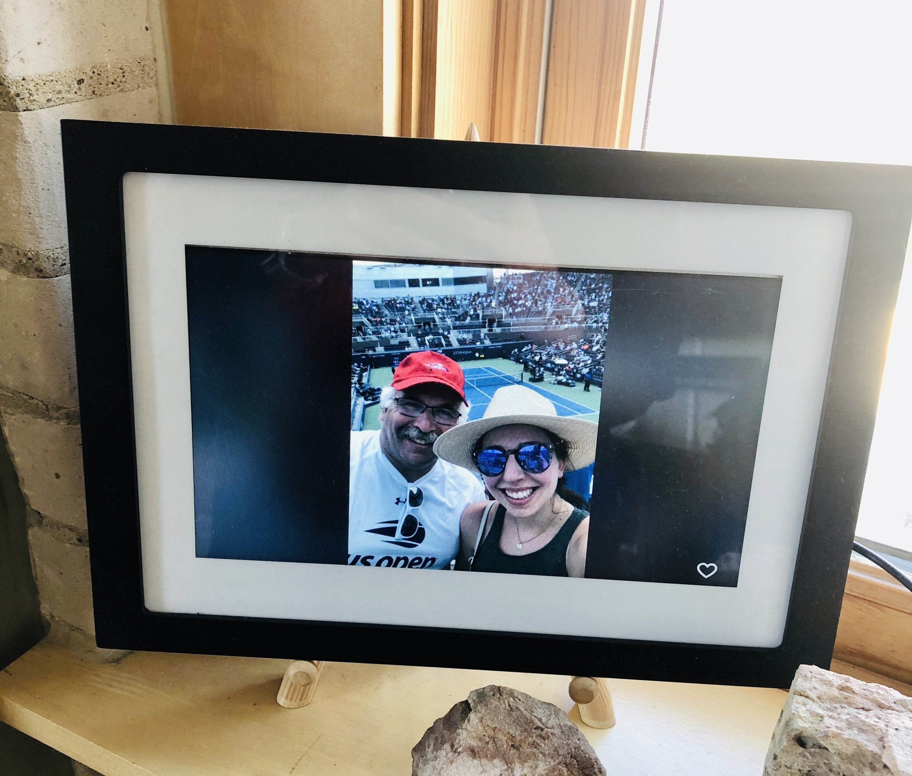 The frame with a white and black frame around the digital screen in the author's parent's home with a picture of her and her father at a tennis match