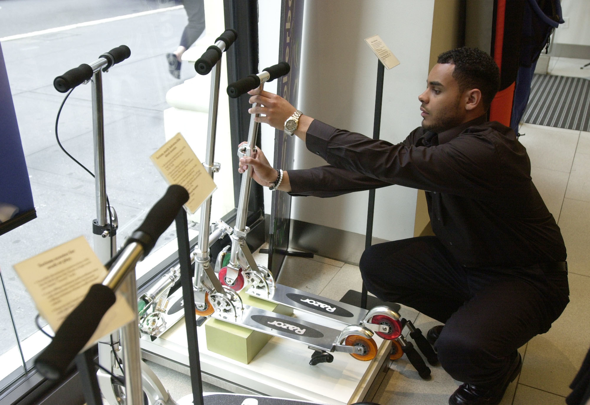 An employee setting up Razor scooters as a window display at a Sharper Image