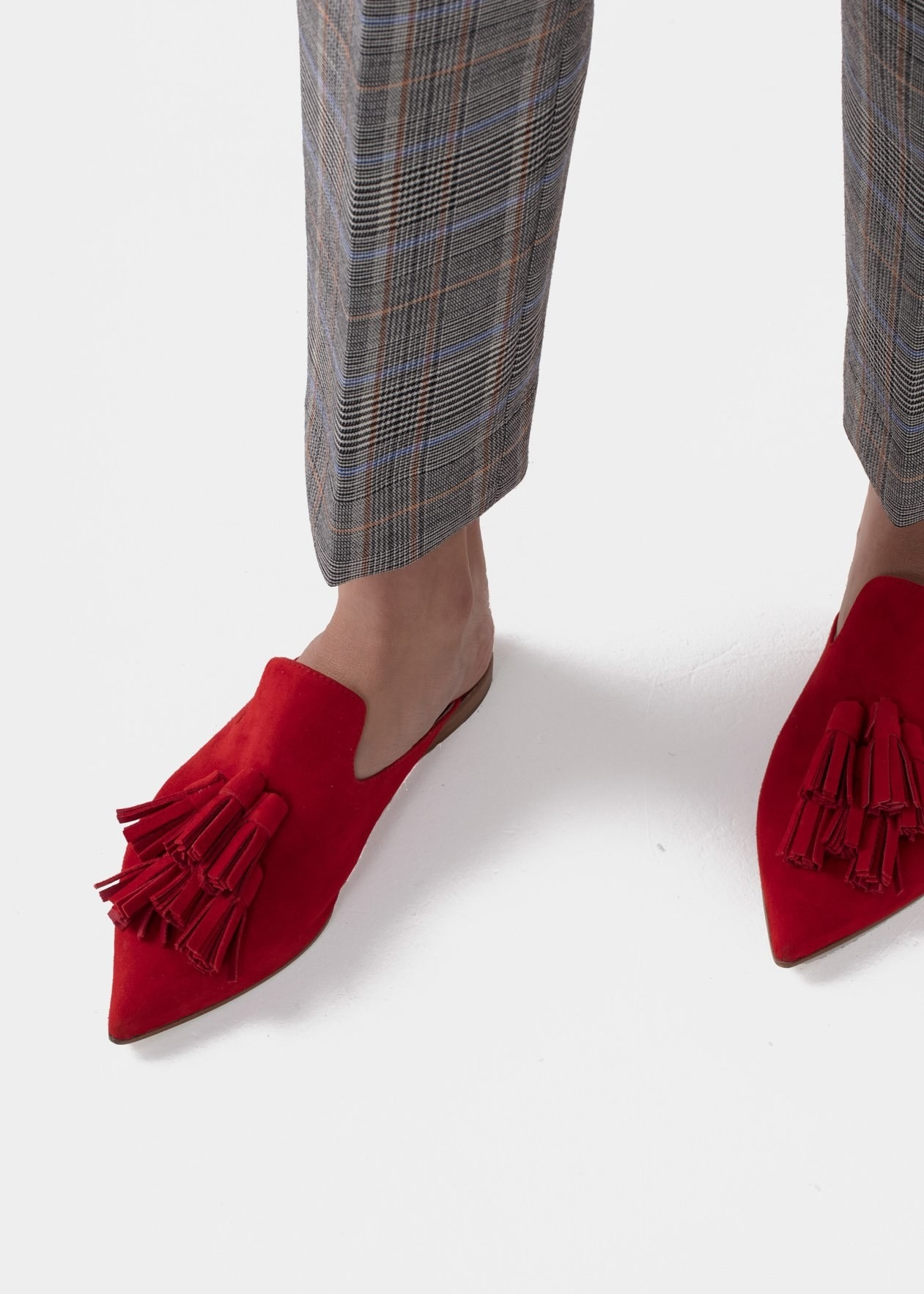 The pointed toe red slip-on loafers with a collection of tassels on the top center