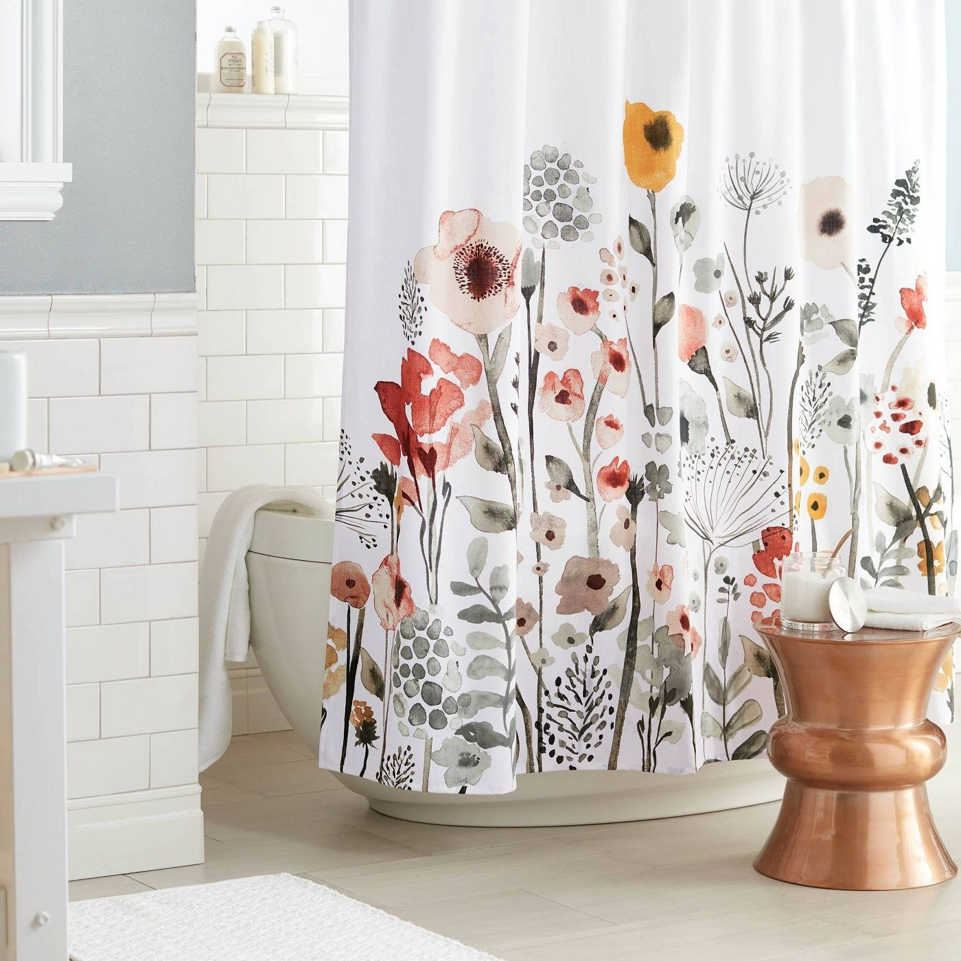 a white shower curtain with a floral pattern