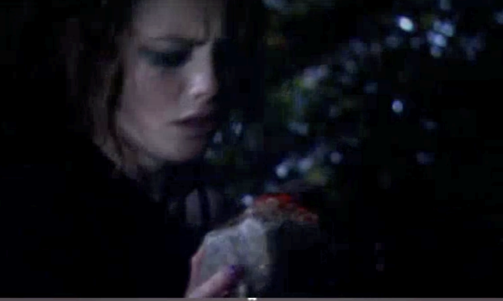 Effy holding a bloody rock after hitting Katie with it