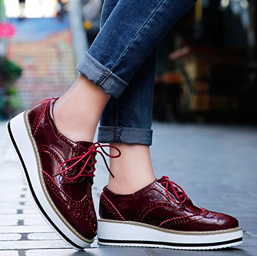Model wears red oxford platform shoes with cuffed jeans