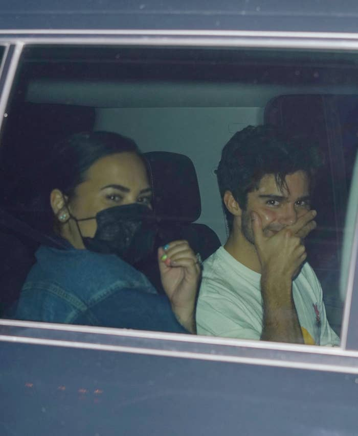 Demi wearing a mask, and Max smiling and covering his mouth in a car