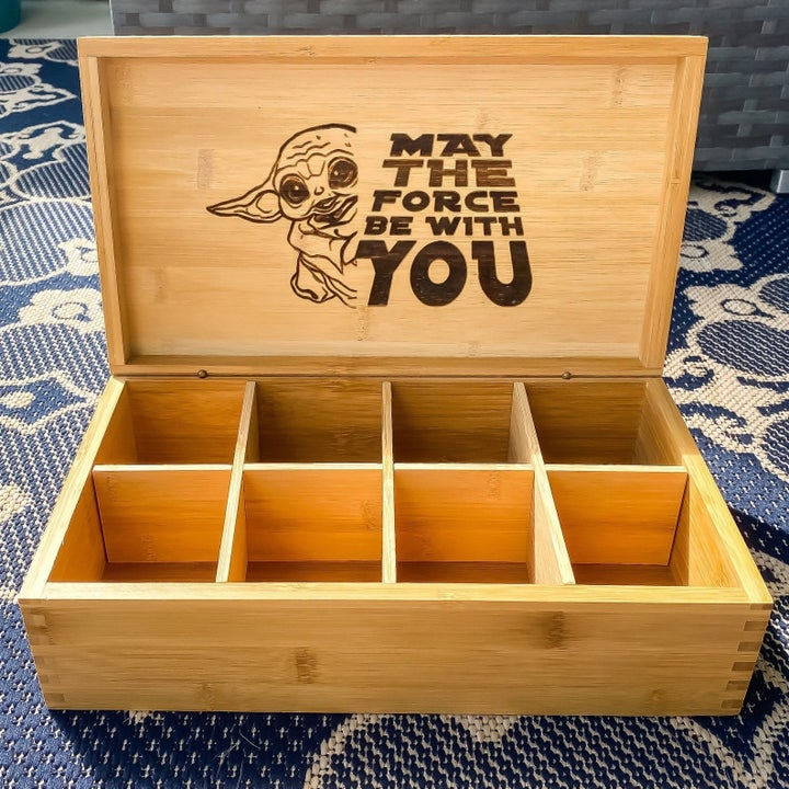 """the inside of the tea box featuring an engraved baby yoda and the words """"may the force by with you"""" on it"""