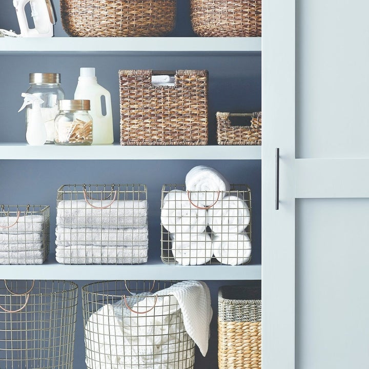 wire milk crates sitting next to each other on a shelf holding extra towels and linens