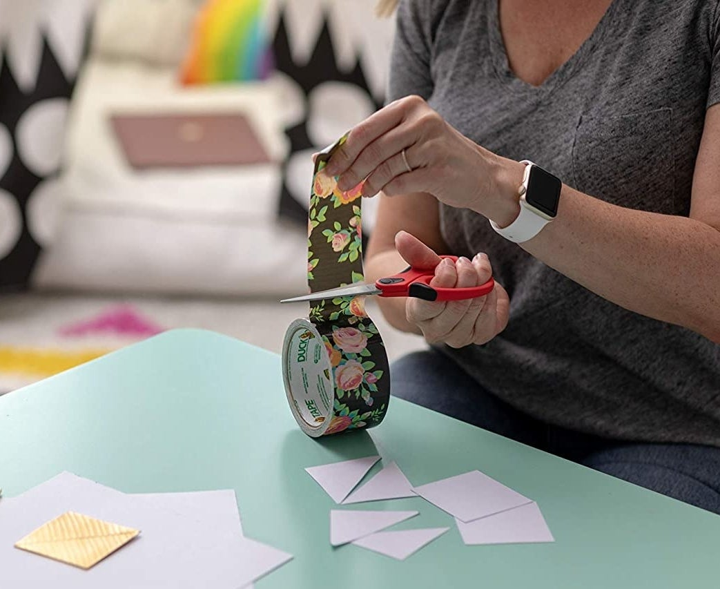 A person cuts floral duct tape