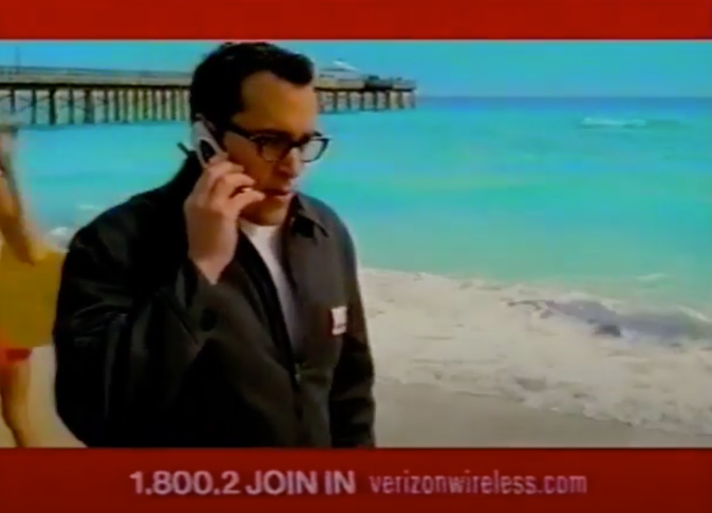 """A screengrab of Verizon commercial featuring  the spokesperson saying """"Can you hear me now?"""" into a flip phone"""