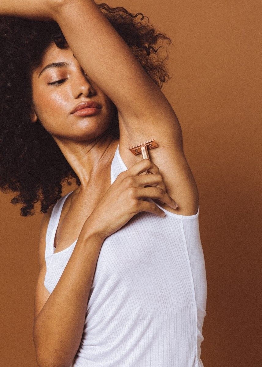 Model using the rose gold-colored razor on their armpit