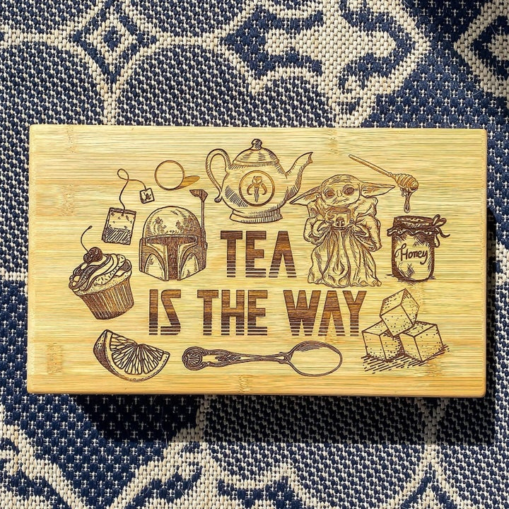 """a wooden tea box with star wars characters engraved in it and """"tea is the way"""" on it"""