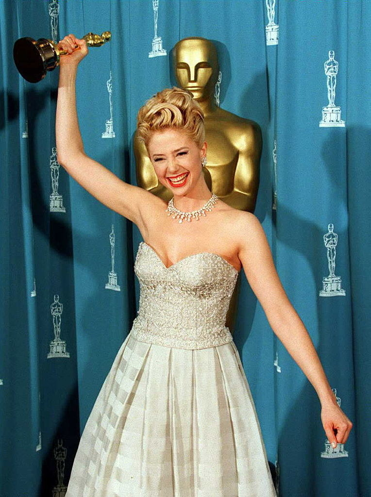 Mira Sorvino happily holds her Oscar in the air at the Academy Awards in 1996