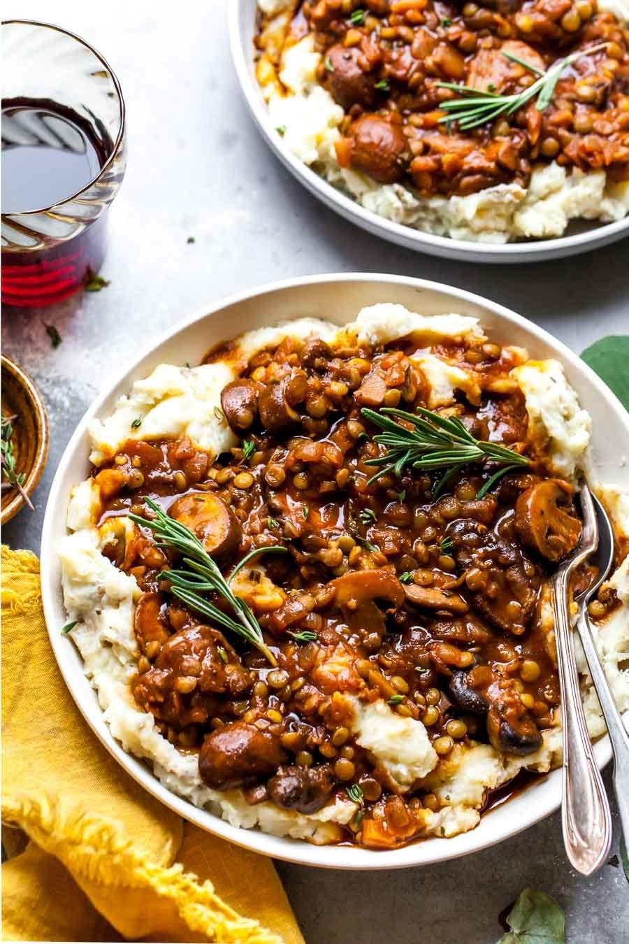 A bowl of mashed potatoes topped with a lentil and mushroom stew, garnished with rosemary.
