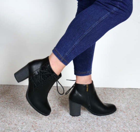 Reviewer wears black booties with a lace-up detailing on the side and a two-inch heel