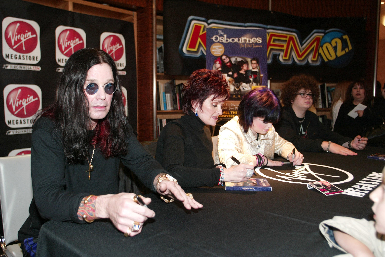 The Osbournes at a table signing DVDs at a Virgin Megastore