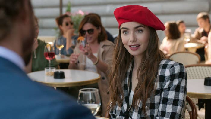 Emily talking to someone offscreen while wearing a beret.