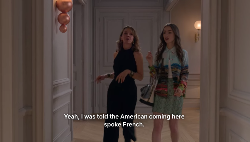 Emily and her new French boss walking down their office hallway.