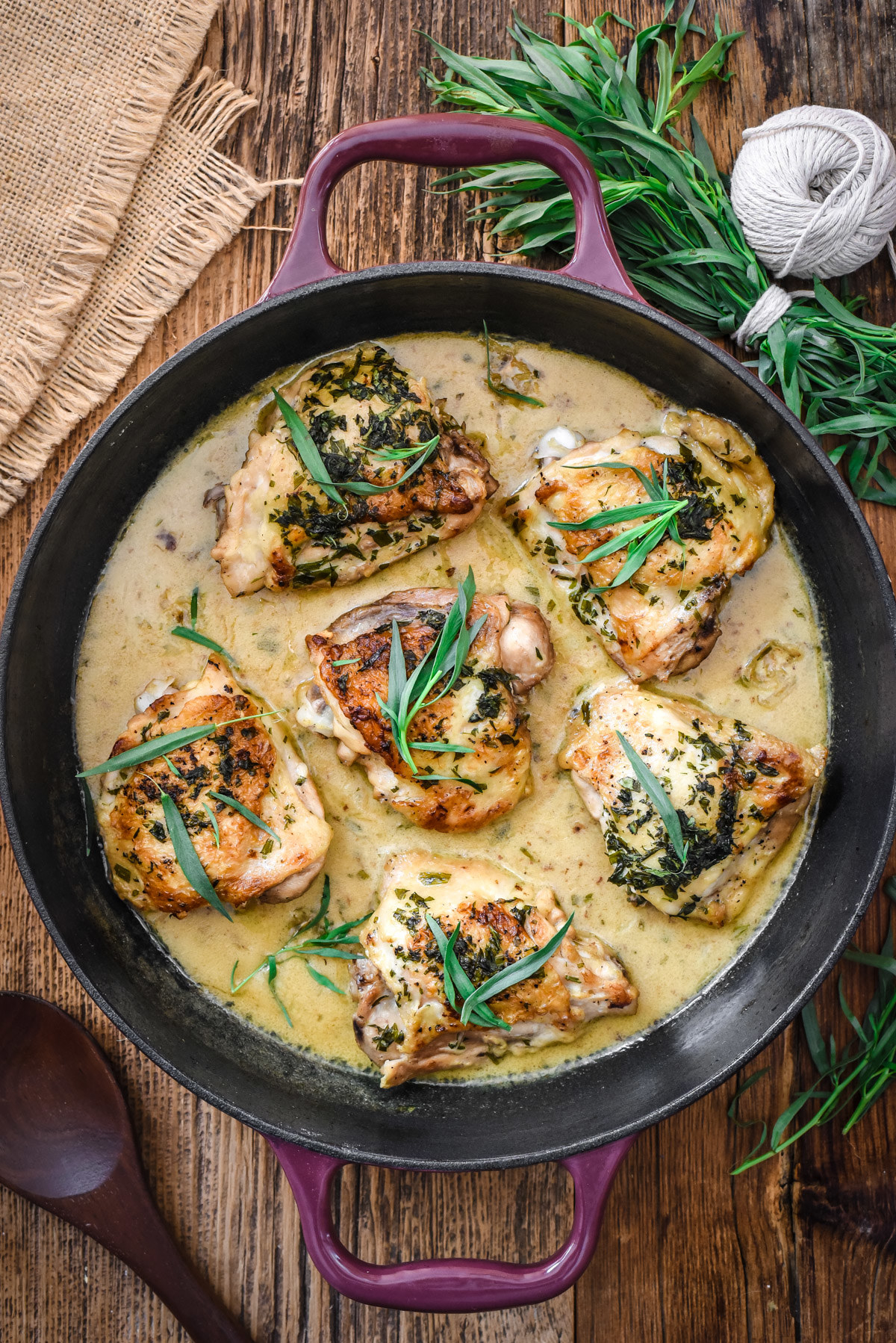 Chicken thighs in a creamy pan sauce garnished with fresh tarragon.