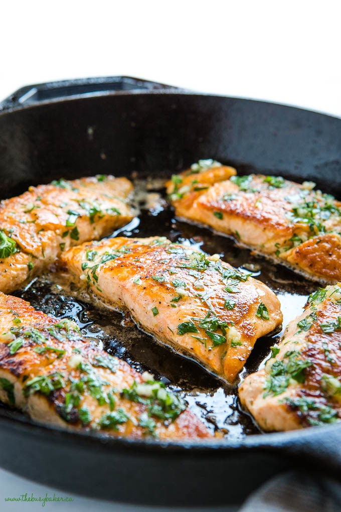 Herb-covered salmon fillets cooking in a cast iron pan.