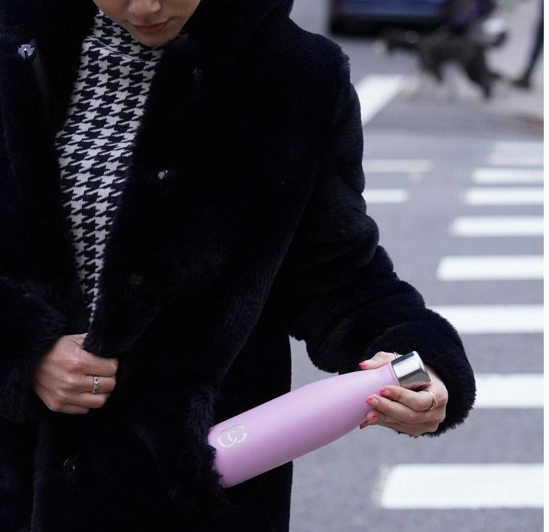 The water bottle in pink, which is cylindrical, opaque, smooth, tapered near the top, and has a metal cap with the UV technology inside it