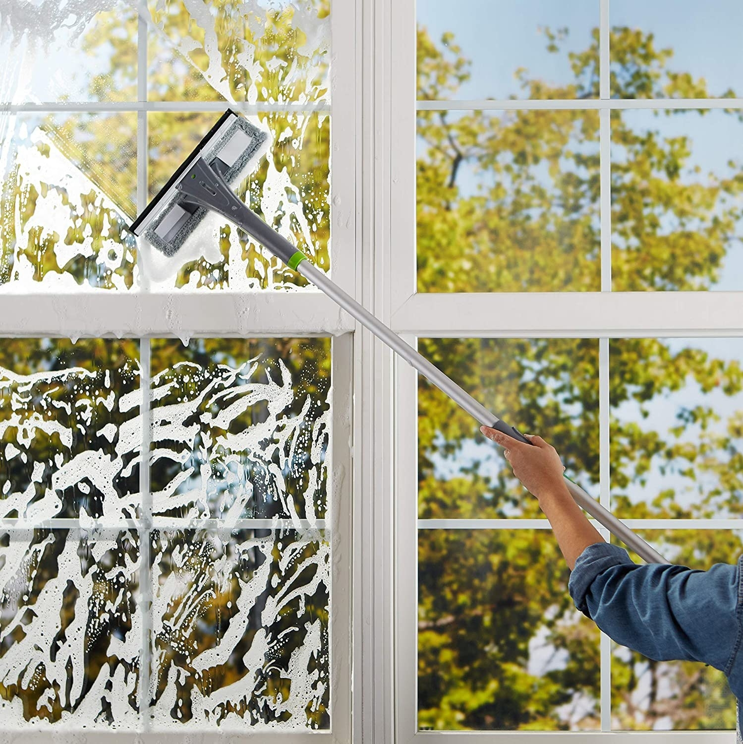 A person using the extendable squeegee to clean windows.