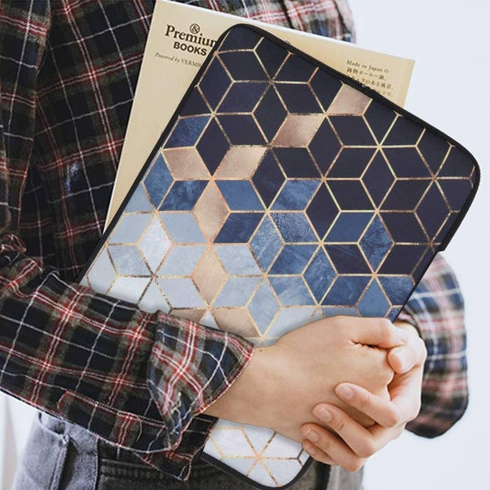 A person holds a laptop inside a geometric printed sleeve with gold accents