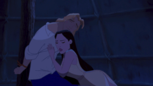Pocahontas clutching John's chest as he leans over, tied to a pole