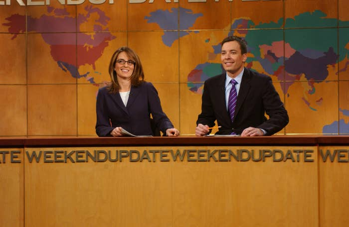 A photo of Tina Fey and Jimmy Fallen sitting at the Weekend Update desk