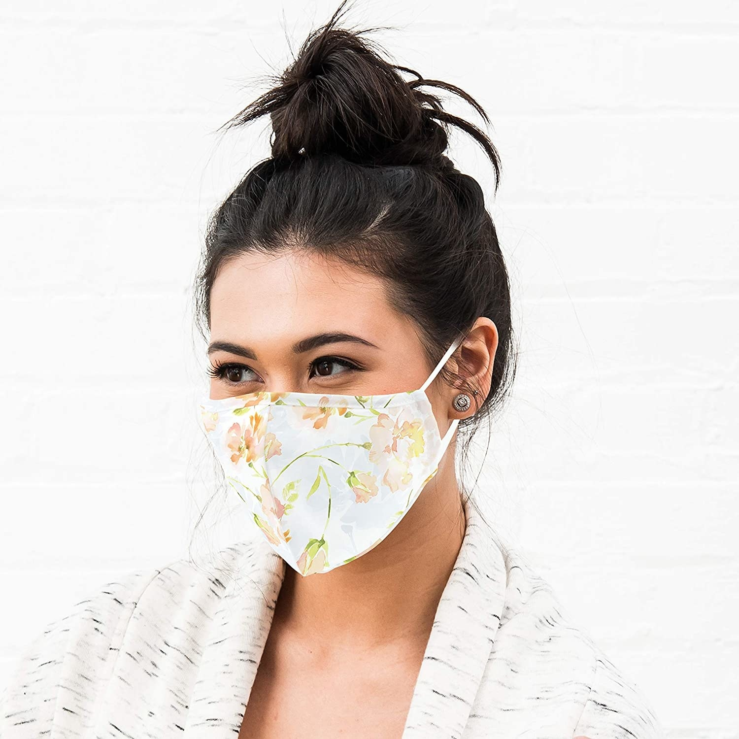 A person wears a face mask with elasticized bands on the ears