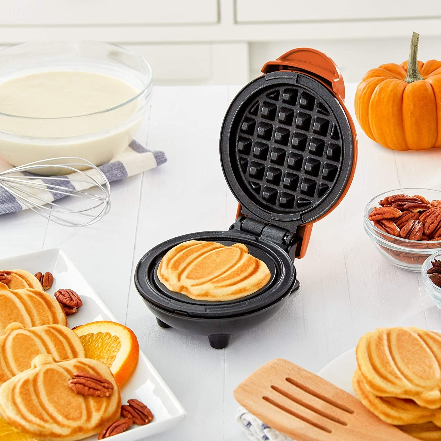 A pumpkin-shaped waffle in the waffle maker, surrounded by stacks of them and batter