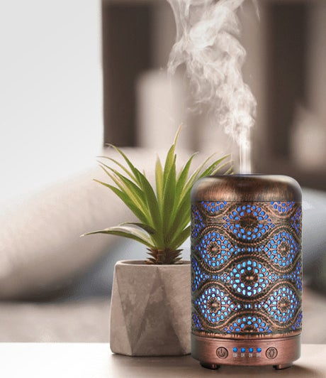 An essential oil diffuser with a pretty hammered pattern on a table