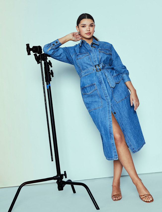 Model wearing the button-up denim dress with utility pockets and a tie waist belt