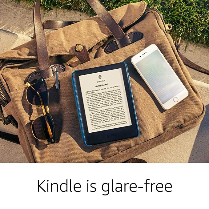 Kindle lying on a bag, with sunglasses and a phone near it.