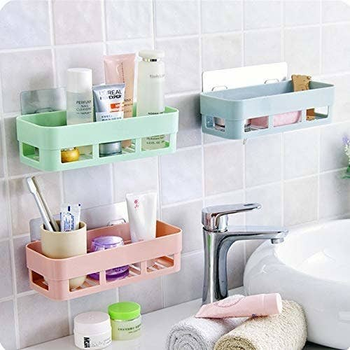 Three pastel adhesive shelves on a bathroom wall with miscellaneous items in them.