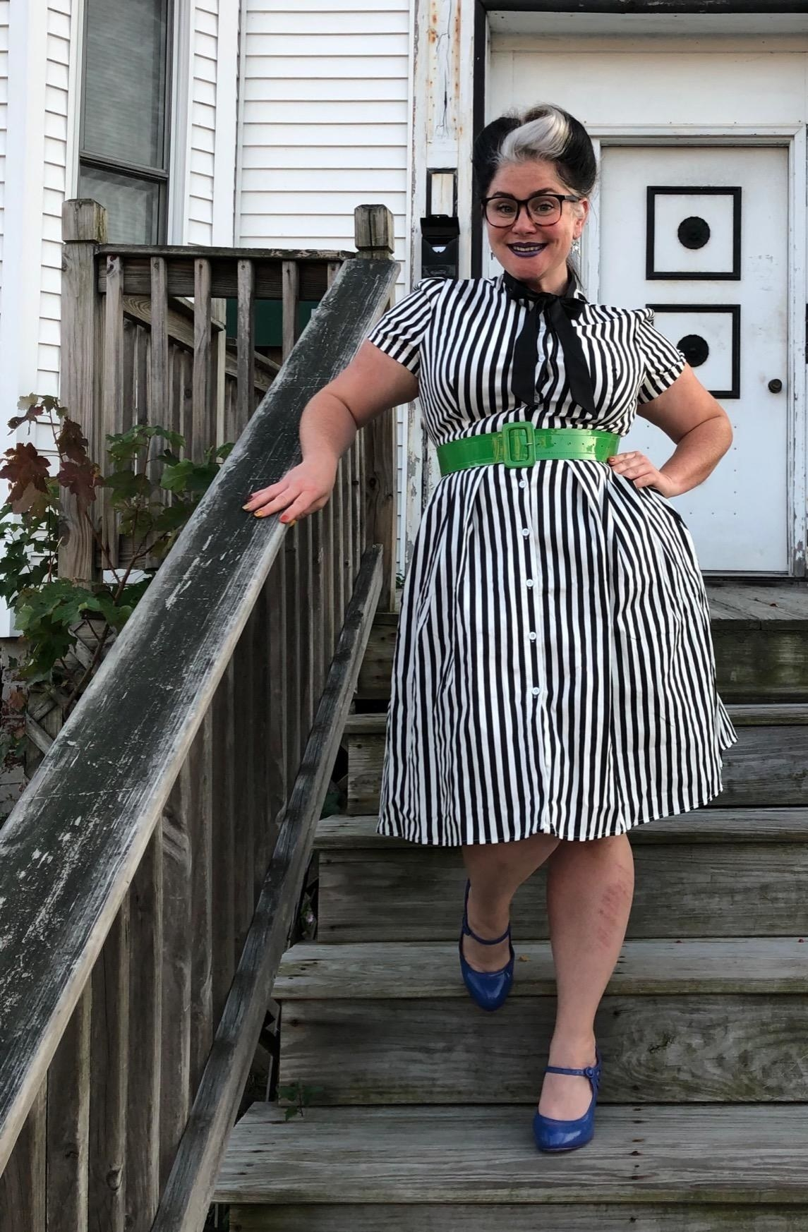 Reviewer wearing the knee-length short-sleeved dress with black and white vertical stripes all over it