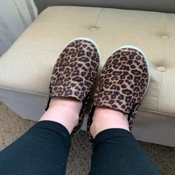 Reviewer wears brown leopard-print slip-on sneakers with black leggings