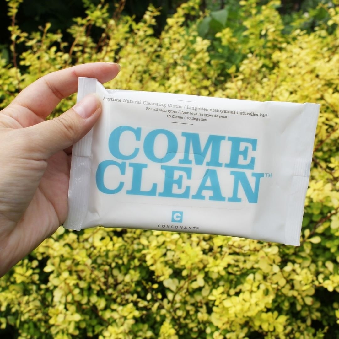 A person holds a package of the wipes against a bright floral background