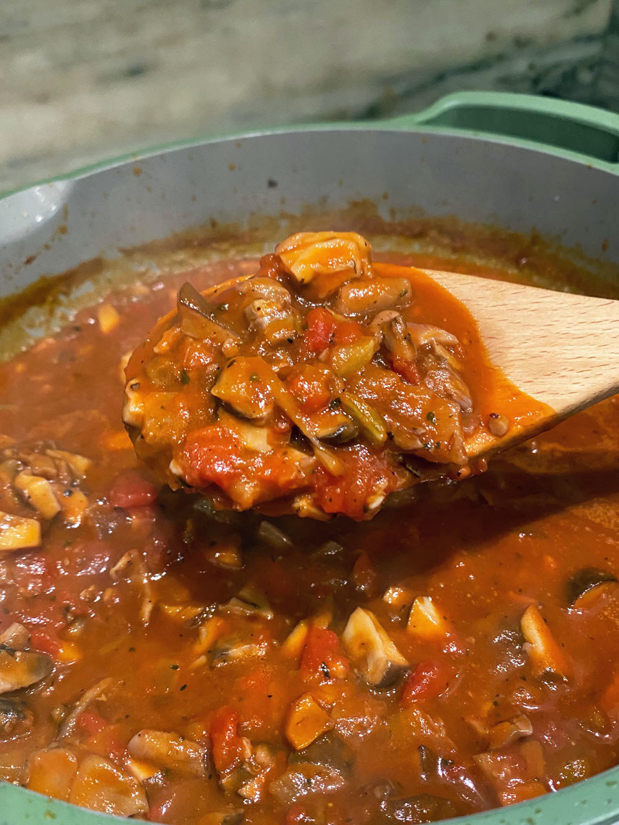 A wooden spoon holding a scoop of the mushroom Bolognese sauce.