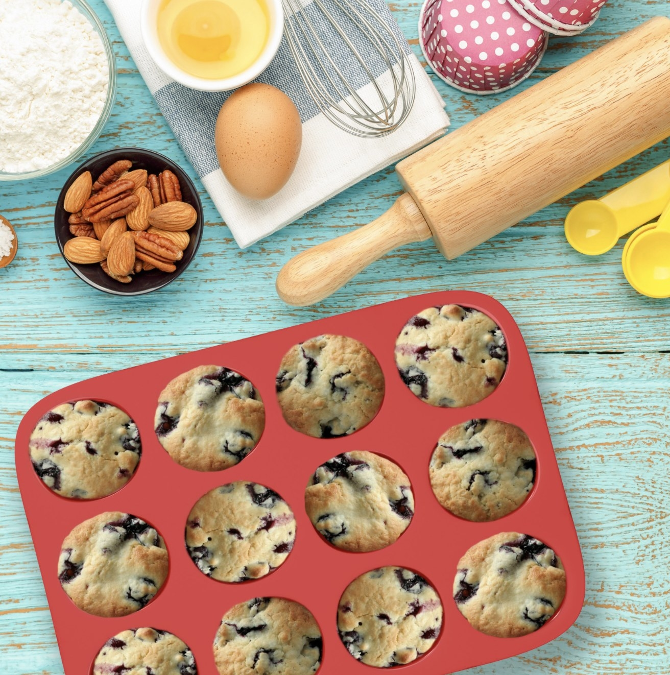 A red silicone baking tray on a kitchen counter with twelve blueberry muffins inside