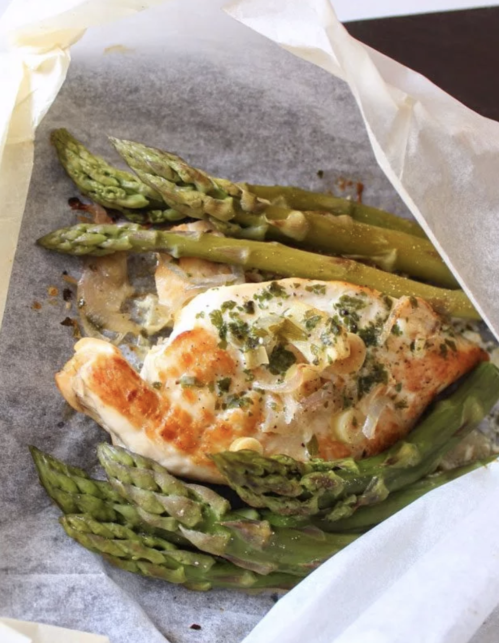 A parchment paper packet filled with asparagus stalks and a chicken breast.