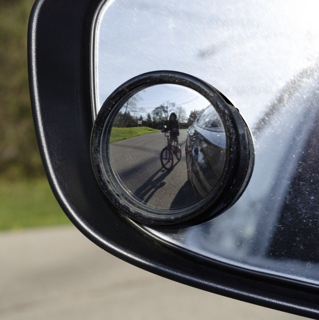 A blind spot mirror attached to a side-view mirror of a car with a cyclist in the reflection