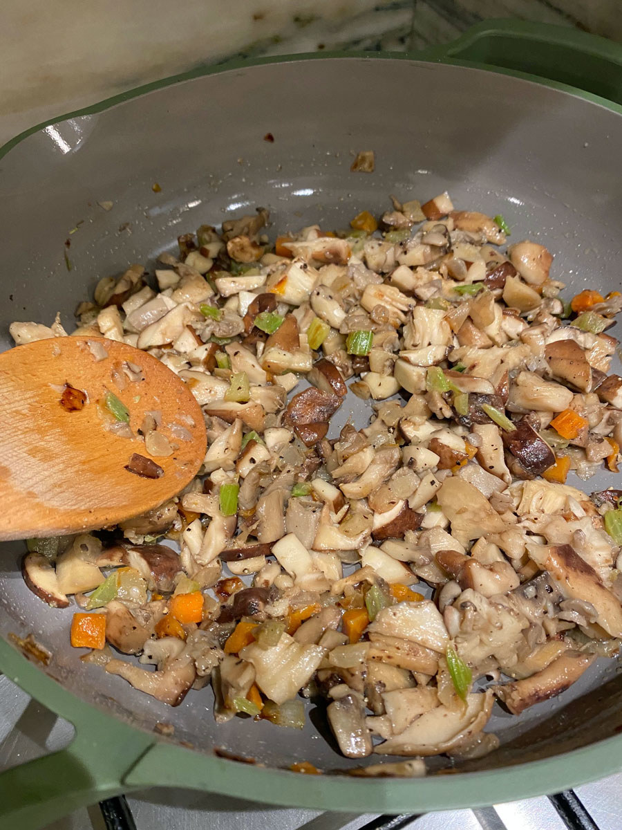 Mushrooms browning in a skillet with cooked carrots, celery, and onion.