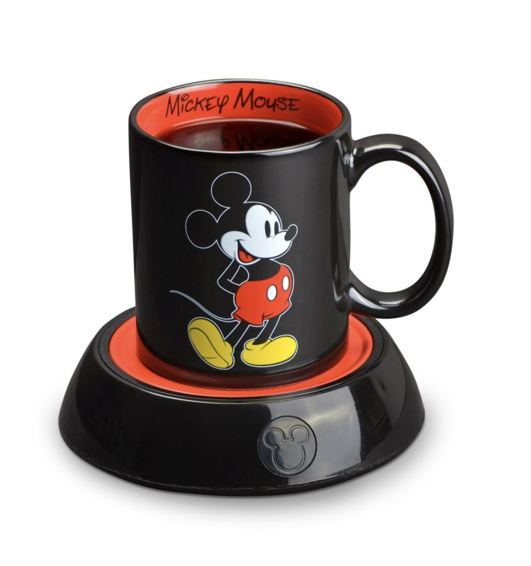 A black mug with Mickey Mouse printed on the front sitting on top of a black and red mug warmer with the mouse ears emblem