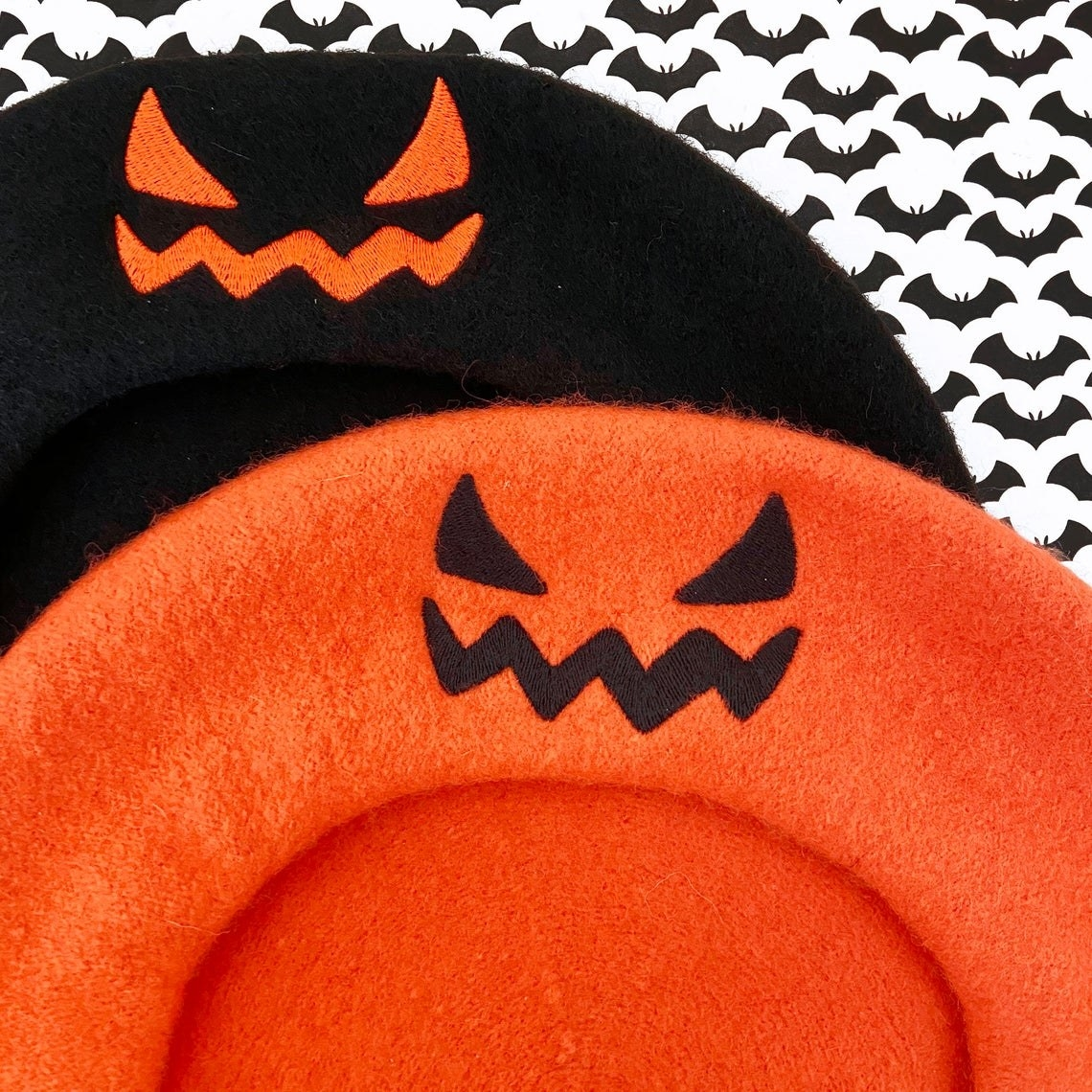 black and orange berets with small jack o lantern faces on the front