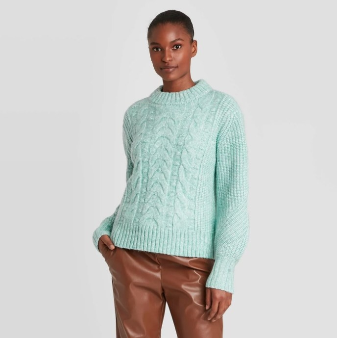 Model wearing light blue knit sweater with brown pleather pants