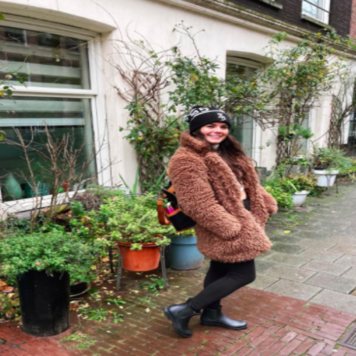 Reviewer wears black Chelsea rain boots with black leggings, a brown teddy coat, and a black beanie while enjoying a rainy day in Europe